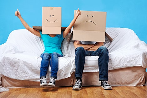 A cheerful woman and unhappy-looking man sit on a sofa  with cardboard boxes on their heads on which their faces have been drawn