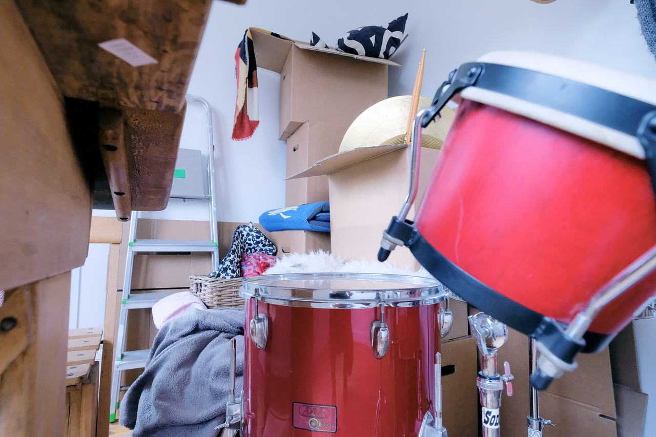 Close up of a drum kit with all kinds of hobby-related gear in the background