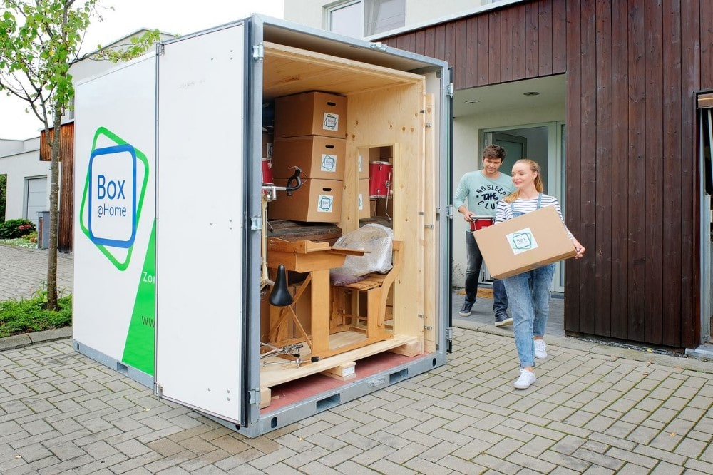 A young couple are busy loading the Large Box that is waiting at their door